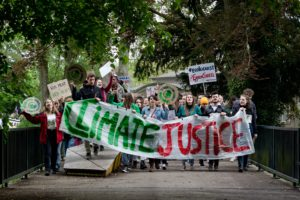 A large group of young people hold a climate justice banner